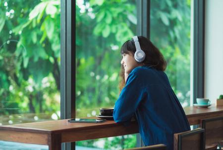 Hörende Musik der glücklichen asiatischen zufälligen Frau mit Kopfhörern nahe Fenster am Caférestaurant, Lebensstil des Digitalzeitalters, kühlen das Leben heraus.