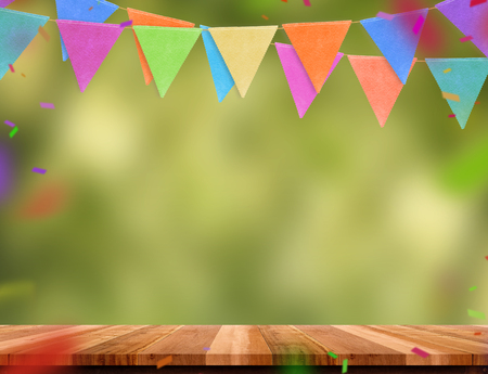 Banner de bandeira colorida e confetes na mesa de madeira com fundo de bokeh árvore verde borrão, modelo de simulação para montagem de product.party guirlanda pano de fundo de férias para design de exibição