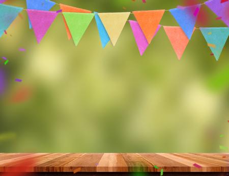 Bunte Flaggenfahne und -konfetti auf hölzerner Tabelle mit Unschärfegrün-Baum bokeh Hintergrund, Schablonenspott oben für Montage des Produktes Partygirlanden-Feiertagshintergrund für Anzeigedesign