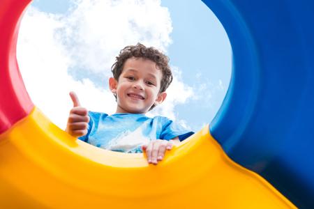 chłopiec dziecko kciuki w górę i zabawa na zabawce wspinaczkowej dla dzieci na szkolnym boisku, powrót do zajęć szkolnych, patrząc w górę widoku.