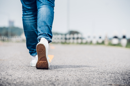 Close up woman wear jean and white sneaker walking forward on highway road in sunny day,Alone travel or solo traveler concept.