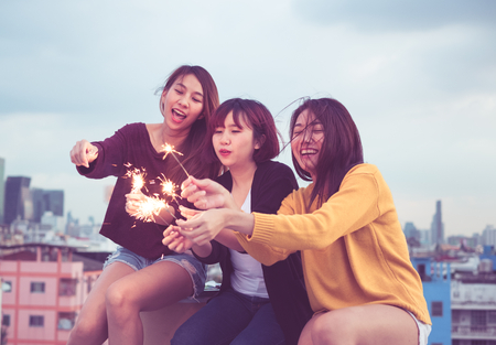 Happy group of asia girl friends enjoy and play sparkler at roof top party at evening sunset,Holiday celebration festive,teeage lifestyle,freedom and fun