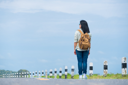 Traveler with backpack looking at blue sky,asia woman backpacker standing on road and looking forward to see way,freedom journey concept,hitchhiker travel Standard-Bild