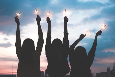 Silhouette heureux groupe d'amis fille asie profiter et jouer sparkler lors d'une fête sur le toit au coucher du soleil en soirée, célébration de vacances festive Banque d'images - 90090607