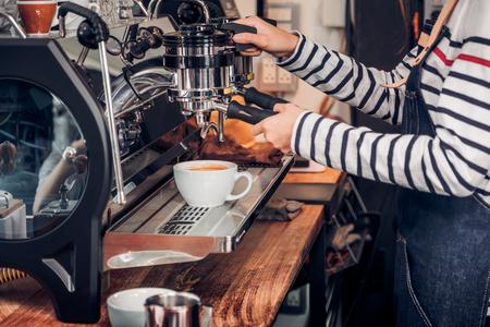 Bliska kobieta barista robi gorącej kawy z maszyny w barze licznika w restauracji kawiarni, koncepcja usługi żywności i napojów. Zdjęcie Seryjne
