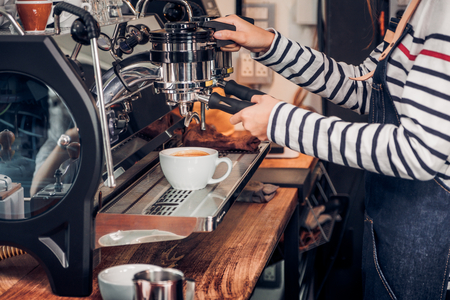 Close up woman barista making hot coffee with machine at counter bar in cafe restaurant,Food and drink service concept. Archivio Fotografico