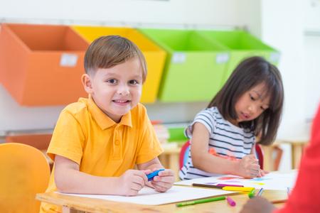 Lächelndes weißes Lernen des kaukasischen Jungenethnie-Kindes im Klassenzimmer mit Freunden und Lehrer in der Kindergartenschule, Bildungskonzept