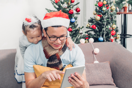 Father and daughter sitting on sofa  and select christmas present and shopping from online store by tablet at xmas party,holiday gift giving festive