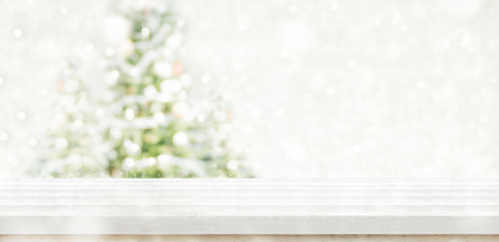 Empty white wooden table top with abstract muted blur christmas tree and snow fall background with bokeh light,Holiday backdrop,Mock up banner for display or montage of product. Stock Photo