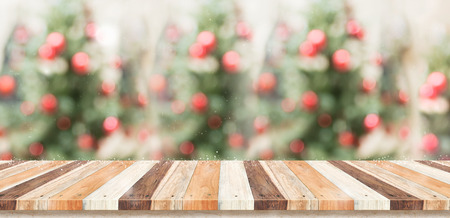 Empty rustic wood plank table top with abstract blur christmas tree red decor ball and snow fall background with bokeh light,winter Holiday backdrop,Mock up banner for display of product or promotion