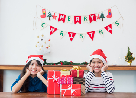 Asia girl friends wear santa hat in Christmas and new year party with group of red gift box with smiling face,Xmas gift giving,Lovely friendship.