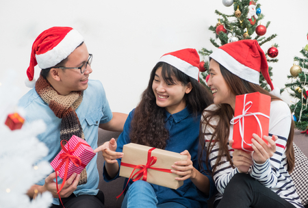 Group of asia friends sitting on sofa celebrate christmas and new year party with gift exchange at decorate tree,gift giving holiday concept.happiness moment of friendship.