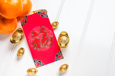 Top view Chinese New year red envelope packet ( ang pow ) with gold ingots and tangerine on white wood table top,Chinese Language on envelop mean Happiness and on ingot mean Wealthy Stock Photo