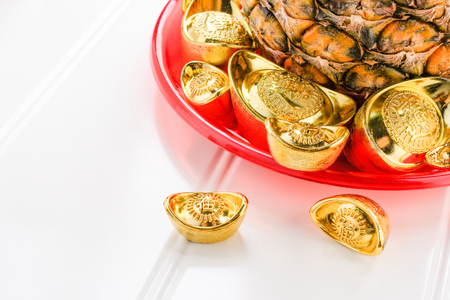Chinese Chinese New year concept,pineapple with group of gold ingots in red tray on white wood table.on ingots mean wealthy.pineapple in chinese language mean luck