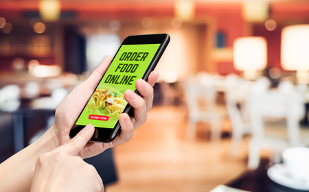 Hand holding mobile with order food online word and order now button with blur table and chair in restaurant with warm light background,Digital Lifestyle concept