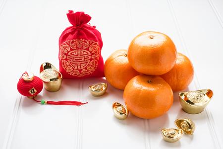 Chinees Nieuwjaar, zak met stof van ang pow rood vilt met goudstaven en mandarijntjes op wit houten tafelblad, Chinese taal betekent geluk en op baar betekent rijk