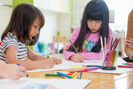 Preschool kids drawing with color pencil on white paper on table in classroom with friends and teacher,Kindergarten education concept