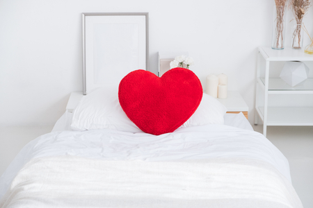 Close up red heart pillow lying on white bed in bedroom.Love valentine honeymoon concept