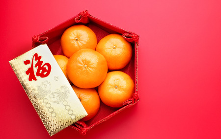 Group of orange tangerine in Chinese pattern tray and envelope packet ang pow on red table top. Chinese new year concep.Chinese Language on envelop is happiness,on ingot is wealthy
