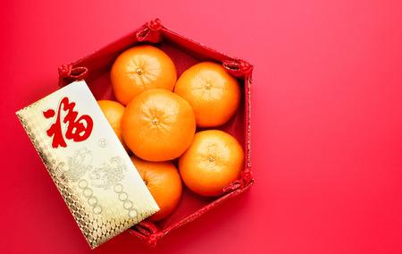 Gruppe der orange Tangerine im chinesischen Musterbehälter und im Umschlagpaket ang pow auf die rote Tischplatte. Chinesisches Neujahr concep.Chinese Sprache auf Briefumschlag ist Glück, auf Barren ist wohlhabend Standard-Bild