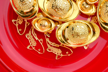 Top view group of golden ingots on red tray with fish pattern .Chinese new year concept,leave space for adding text.Chinese Language on ingot mean wealthy