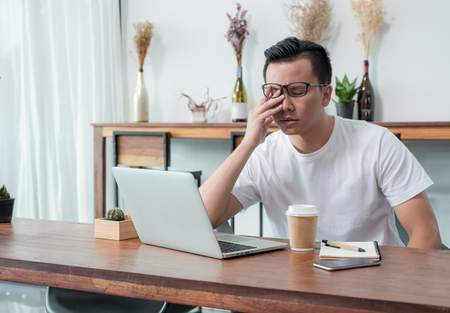 asia casual man cover face with hand upset from work in front of laptop computer in coffee shop,stress emotion concept,work outside office,work at home Stock Photo