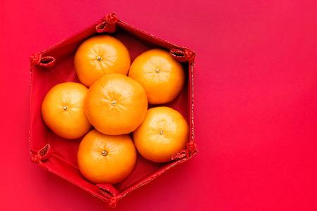 赤いテーブルトップに中国のパターントレイのオレンジ色のみかんのグループ。中国の新年のコンセプト