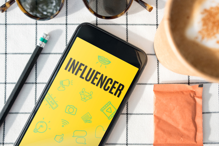 top view influencer feature on mobile screen with coffee cup,sunglasses,pencil on white table cloth.blogger lifestyle.