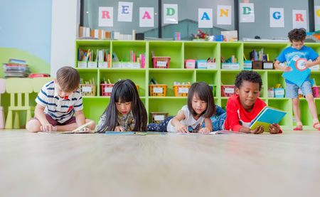 Group of diversity kid lay down on floor and reading tale book in preschool library,Kindergarten school education concept.