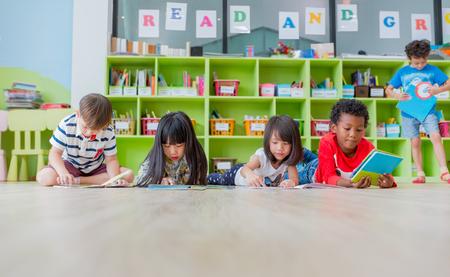 Grupo de diversidad niño acostado en el piso y leyendo el libro de cuentos en la biblioteca preescolar, concepto de educación escolar de jardín de infantes. Foto de archivo
