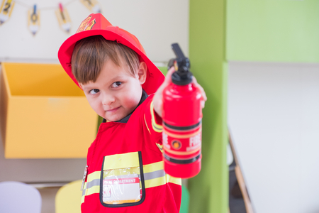 Caucasian boy kid dress up to fireman and use speaker at roll play classroom,Kindergarten preschool education concept. Archivio Fotografico
