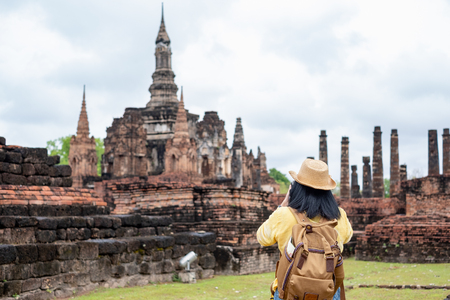 Asian tourist woman take a photo of ancient of pagoda temple thai architecture at Sukhothai Historical Park,Thailand. Female traveler in casual thai cloths style visiting city concept. Stock Photo