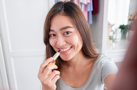 Asian young female blogger recording selfie vlog video with makeup lipstick cosmetic at home online. Influencer on social media concept. Stock Photo