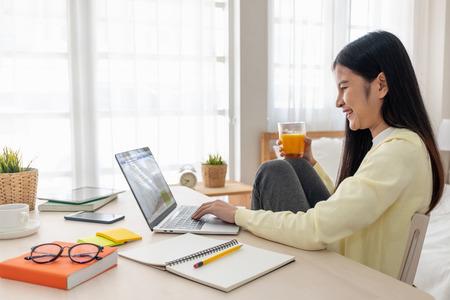 Asiatische Frau sitzen mit den Knien oben verwenden soziale Medien mit Laptop auf dem Tisch und trinken Orangensaft im Schlafzimmer zu Hause Standard-Bild