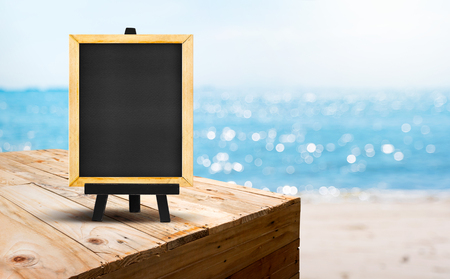 Blank blackboard on wood table food stand with blur sand beach and blue sea with bokeh light background.Template Mock up for summer vacation promotion sale Stock Photo