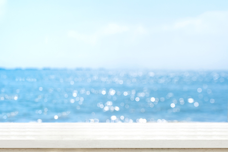Empty plank white wood table top with blur blue sky and sea boekh background,summer holiday backdrop.Mock up template for display or montage of product or content use as panoramic banner in ads