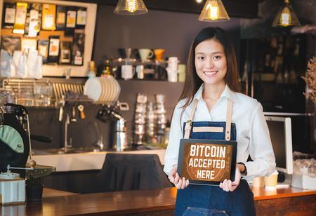 Close up woman barista holding tablet et show bitcoin accepté ici sur l'écran de la tablette au bar du comptoir du café, vendeur café accepter le paiement par crypto currency.digital money concept.Modern serveuse
