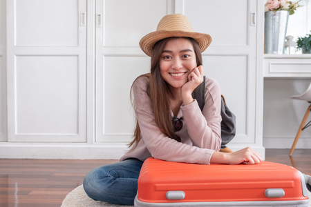 Young asian woman traveler packing stuff in orange suitcase prepare for holiday vacation at home.backpacker travel concept