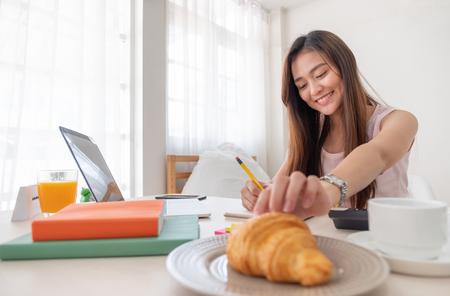 Femme asiatique mangeant un croissant tout en travaillant avec un ordinateur portable sur la table à la maison. Banque d'images