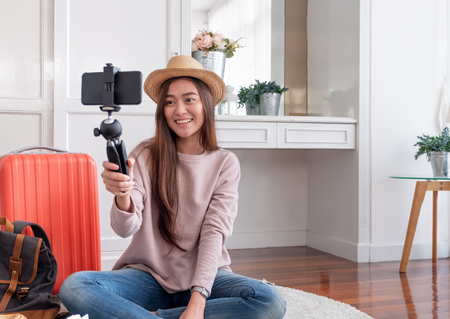 Asian young female blogger recording vlog video with mobile phone live streaming when travel.online influencer on social media viral concept