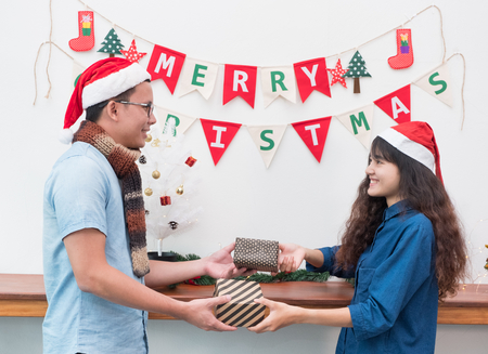 Asian lover couple wear santa hat in merry christmas party and exchange gift box each other with smiling face,Xmas gift giving,holiday celebration festive seasonal Stock Photo