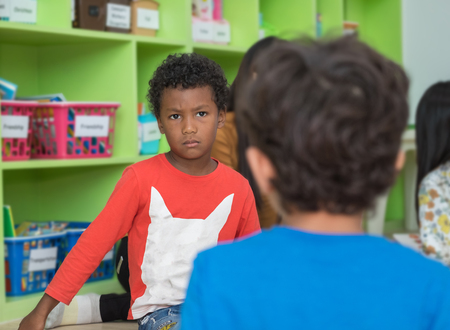 African american boy angry and looking at friend in school library in kindergarten.kids education concept Banque d'images