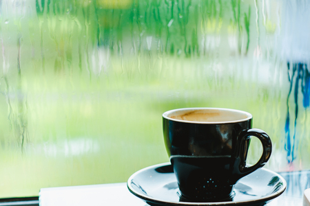 Black coffee cup on table in cafe restaurant near window in garden when raining in garden outside shop,Food and drink concept,Leisure lifestyle