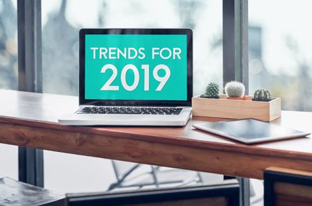 Tendances pour 2019 mot dans l'écran d'ordinateur portable avec tablette sur bois se tenait la table dans une fenêtre avec arrière-plan flou, entreprise numérique ou tendances marketing