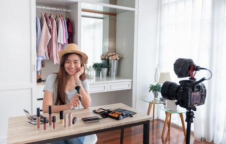 Blogger de sexo femenino joven asiático que graba video de vlog con cosmético de maquillaje en casa influencer en línea en concepto de redes sociales.