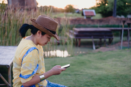 Asian woman wear hat sitting outside use mobile phone at garden with chill out feeling.relax leisure lifestyle
