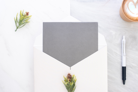 Top view of blank grey card in white envelop with coffee and pine leaf on two layer step of marble table top.Mock up template for display of design.modern business items