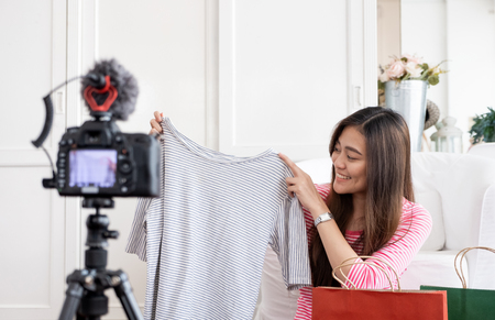 Asian young female blogger recording vlog video with review cloths T-shirt at home online influencer on social media concept.live streaming viral Stock Photo