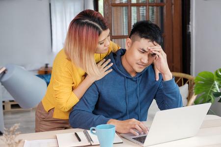 Petite amie asiatique encourageant son petit ami contre le stress tout en travaillant sur le budget de la maison sur un ordinateur portable dans le salon de la maison Banque d'images