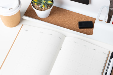 top view of open calendar planner with modern office stationery and take away coffee cup on white desk in office.mock up space of organizer table notebook Stock Photo